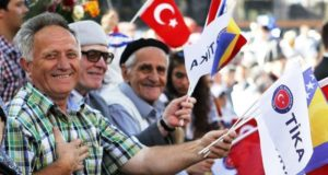 People waving Turkish and Bosnian flags in an opening ceremony of a project by TIKA.